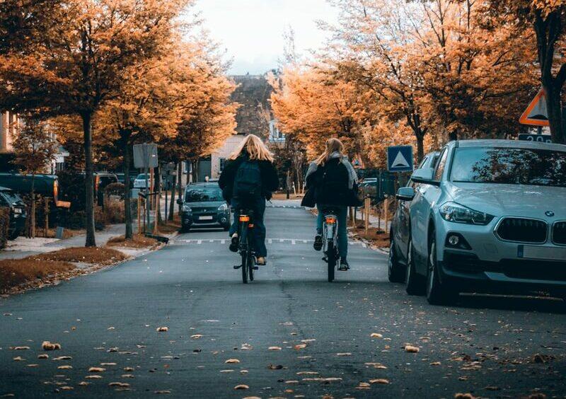 people walking on sidewalk near cars parked on sidewalk during daytime